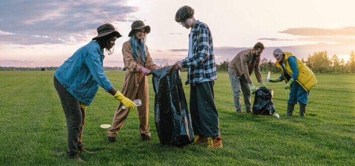 people picking trash on grass field
