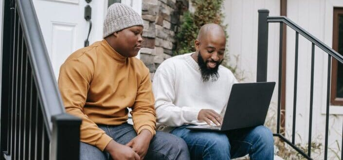 Two guys sitting on stairs with laptop