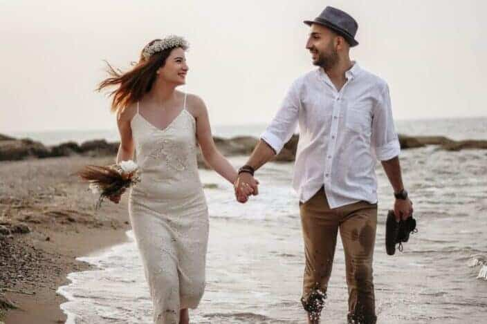 happy couple walking on seaside