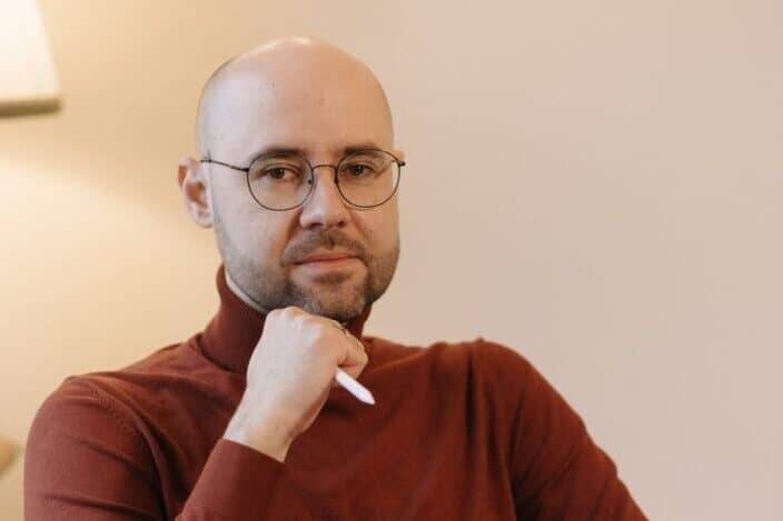 man in sweater wearing eyeglasses and holding pen