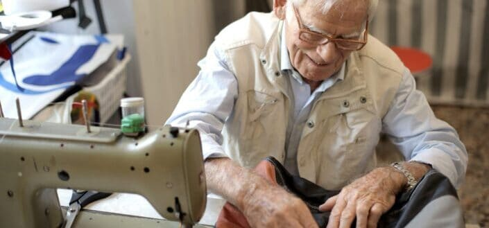 Photo of man sewing