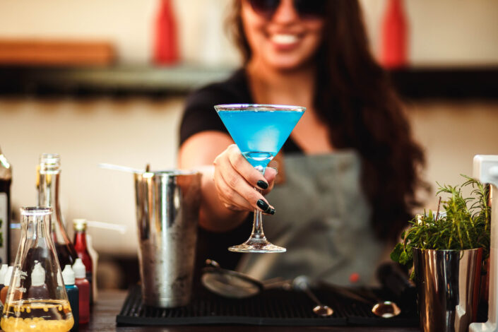 Woman holding cocktail glass with blue liquid