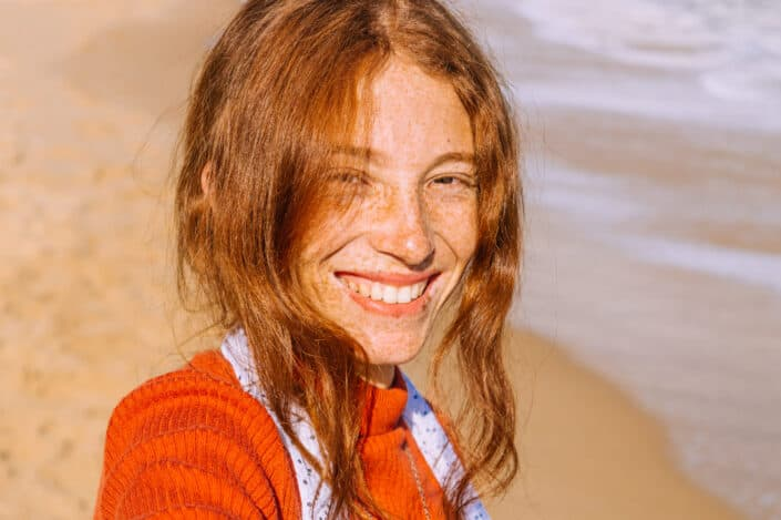 A smiling woman with freckles standing by the beach