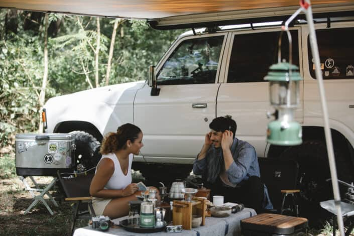 Woman and man listening to music beside a car
