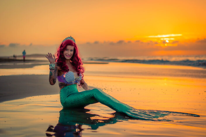 A woman dressed up as a mermaid by the beach