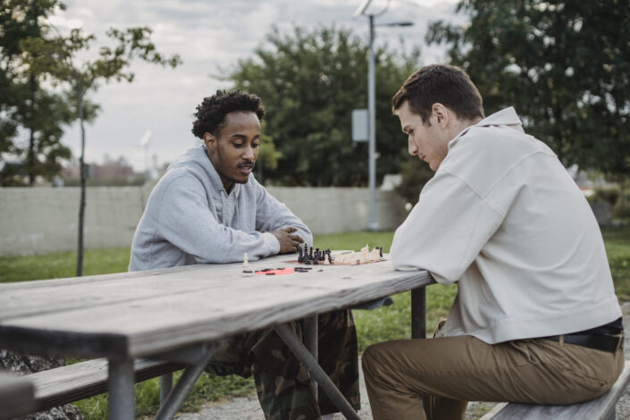 Serious youthful diverse friends playing chess in park