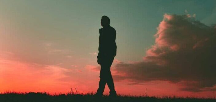 Person's silhouette on a pink-sky background.