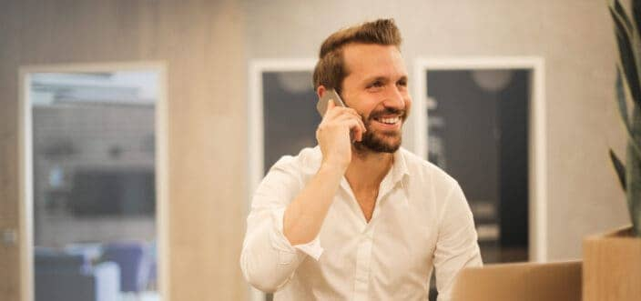 A guy happily talking on a phone.