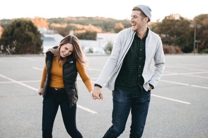 A couple laughing together in parking lot