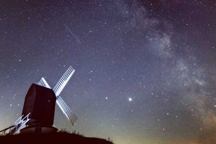 View of windmill with starry sky background.