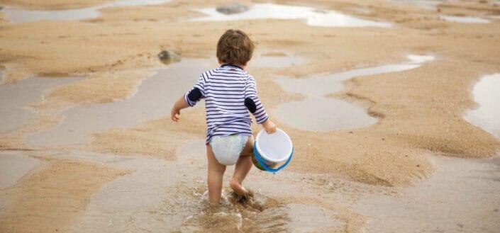 Toddler walking on shoreline