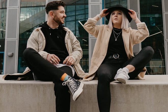 Couple wearing matching clothes sitting on a ledge - unanswerable questions
