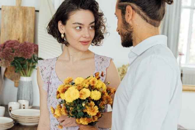 A woman looking at a man offering her flowers - valentines day pick up lines