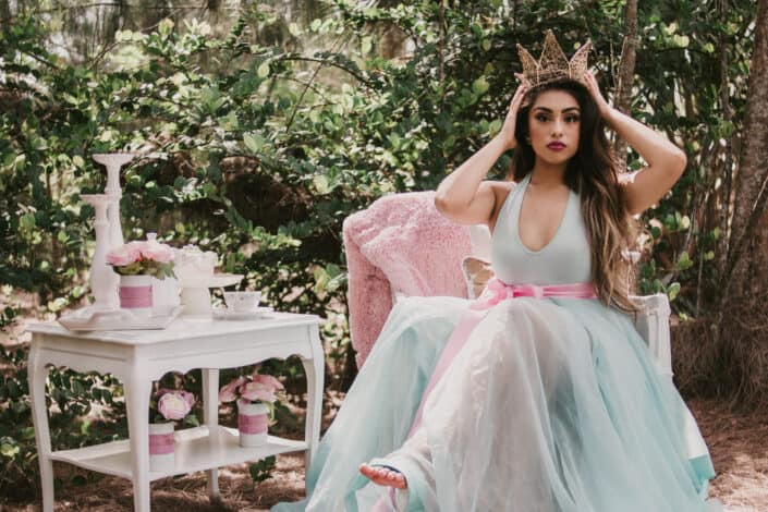 A woman dressed up as a princess, sitting down