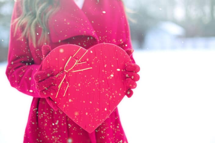 Woman in red long sleeved coat holding a heart shaped box.