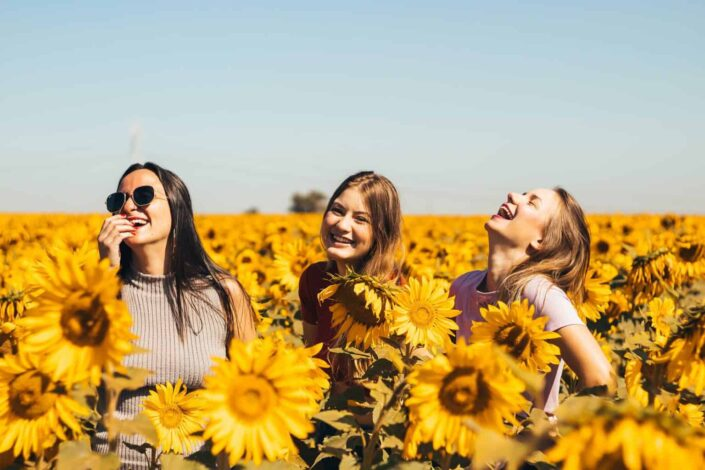 Friends in the middle of sunflower field