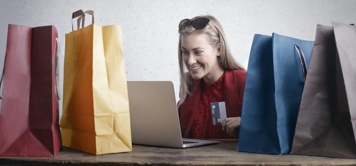 woman smiling at her laptop with shopping bags around her