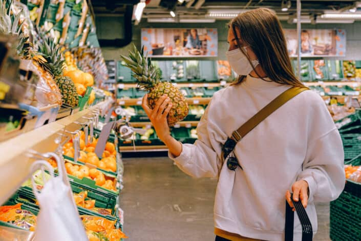 Woman wearing mask in supermarket and looking at a pineapple