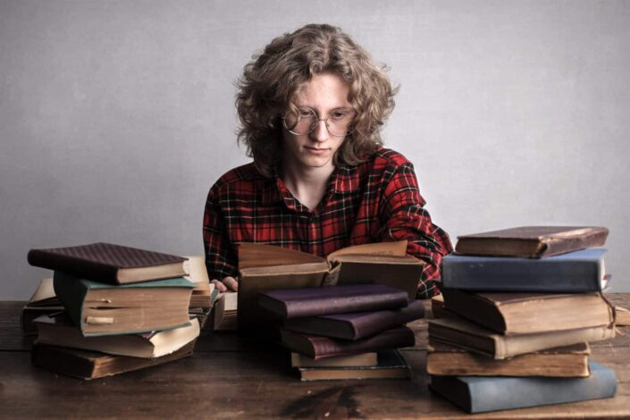 Person reading over pile of books on table.