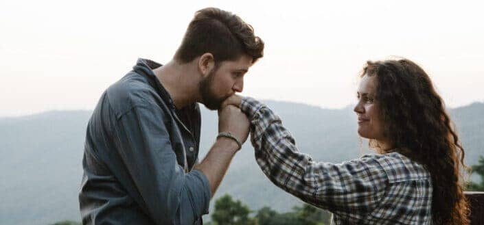 Young man kissing hand of smiling girlfriend in nature