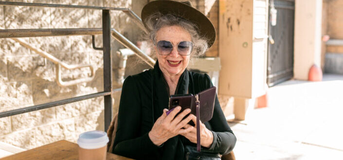 elderly woman in black holding black smartphone