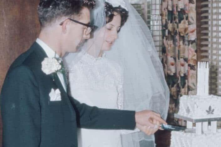 A newlywed couple slicing their wedding cake