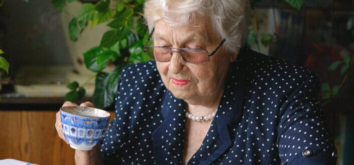 An old lady holding a teacup