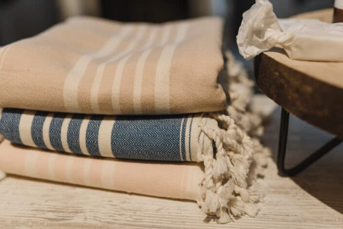 pile of blankets placed on wooden table