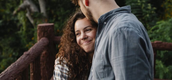 man kissing the forehead of smiling girlfriend