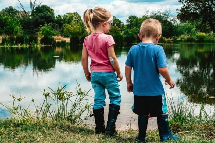 Brother and sister at the edge of a pond looking for tadpoles in the water.