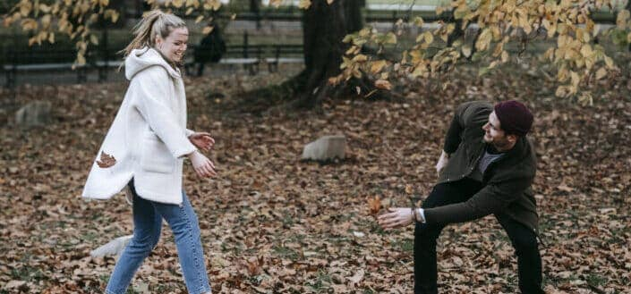Cheerful young couple playing with fallen leaves in park