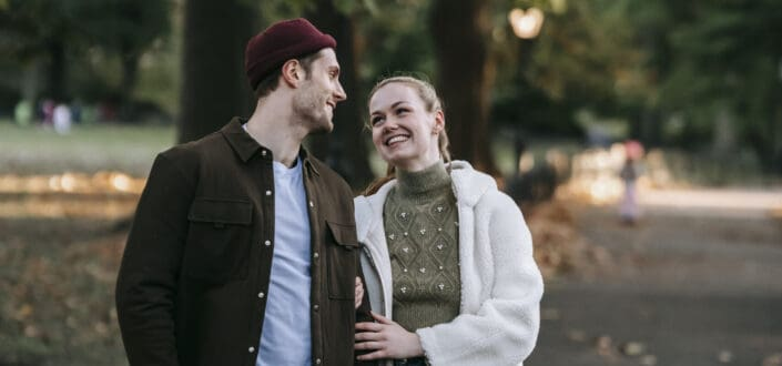 Cheerful young couple standing in park and smiling