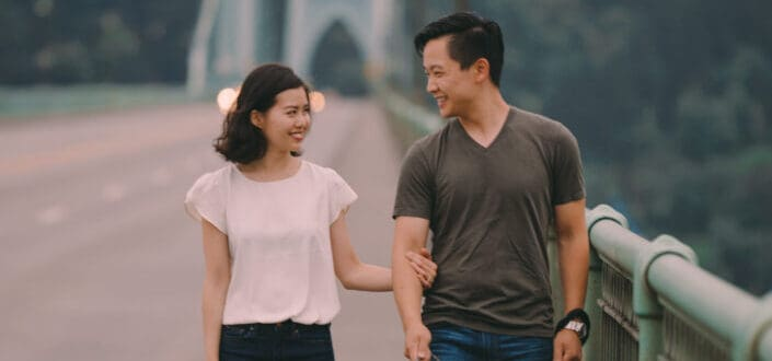 Cheerful young ethnic couple with dog strolling on bridge near green mountains