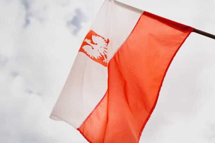 Colorful flag of republic of Poland under cloudy sky