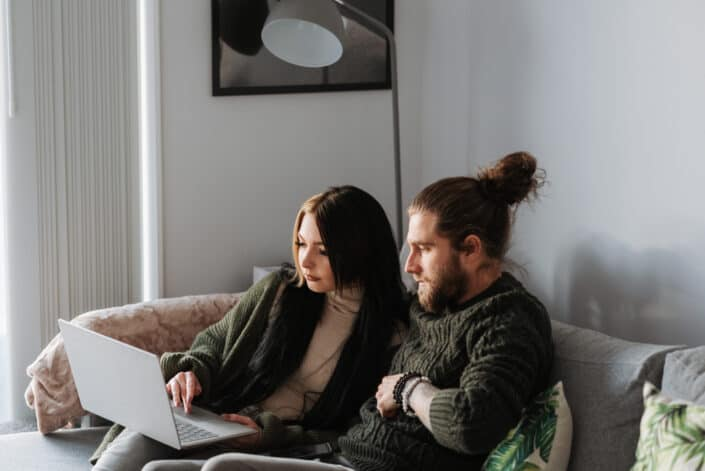 couple surfing the internet via laptop