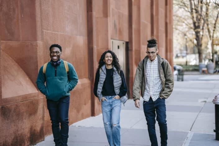 friends walking near an orange building