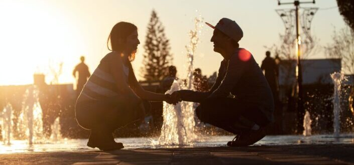 man and woman sitting on water fountain during sunset