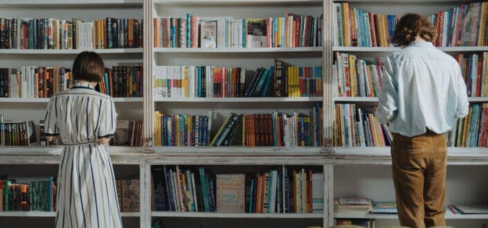 man and woman standing in front of a bookshelf