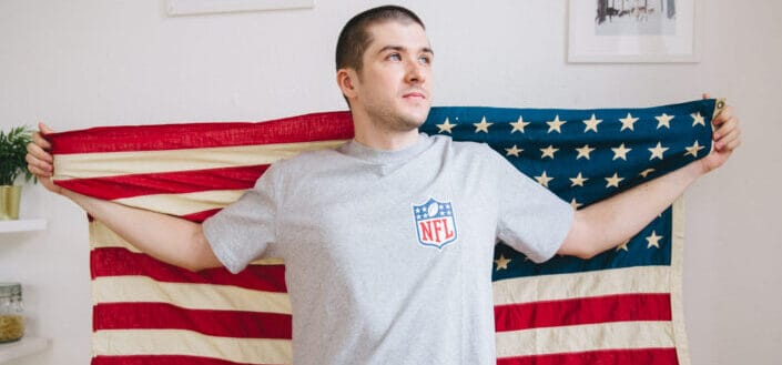 man in grey shirt holding an American flag