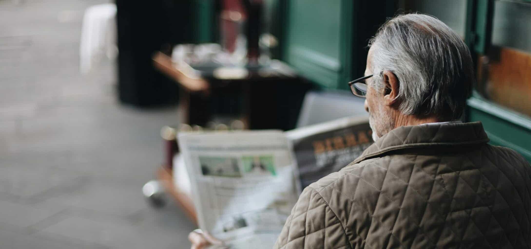 Man sitting while reading newspaper