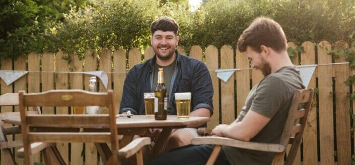 cheerful men chatting on backyard and drinking beer