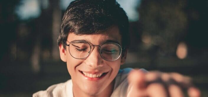 selective focus photography of smiling man wearing eyeglasses