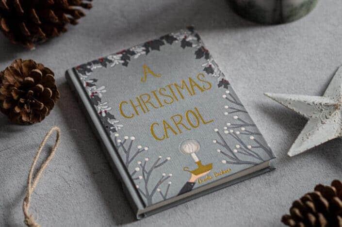 a Christmas carol book near a candle