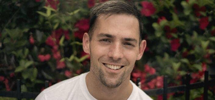 Photo of man wearing white shirt and smiling