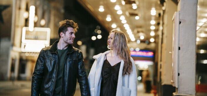 Positive couple walking near station in night