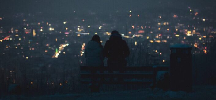 Two persons (a couple?) are having a deep talk at night above the city lights of Stuttgart, Germany