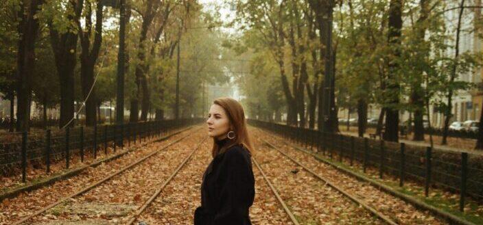 Woman in black coat standing on train rail