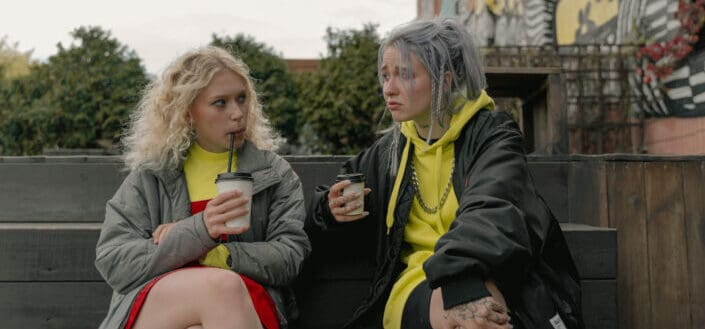 Two women sitting on bench drinking coffee