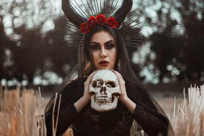 Woman with horns holding a skull