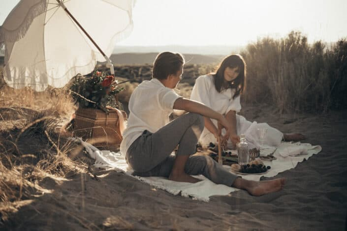 Young couple having picnic on sandy beach